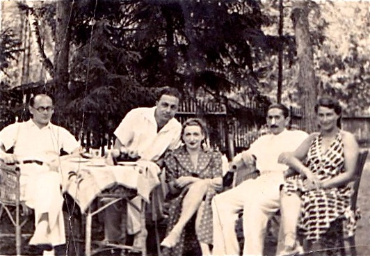 A surviving pic of my parents, with friends, in a garden in or outside Warsaw, quite possibly before I was born: my mother in the center seat, showing off her legs; my father, with his black mustache, on her right; the men in white -- for tennis?